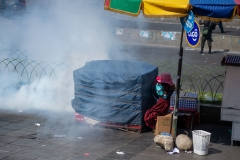 La Paz, Bolivia. 21st Nov 2019. A woman tries to protect herself from a tear gas grenade that landed just next to her stall. Mobile riot Police units fired the gas at protesters who tried to reach the main square of La Paz carrying the coffins with the remains of victims killed on November 19th in the aftermath of a combined Police/ military operation in Senkata. At least 9 people died and further 30 were injured. Radoslaw Czajkowski/ Alamy Live News