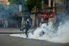 La Paz, Bolivia. 13th Nov 2019. A Police officer kicks back a tear gas grenade that has been kicked back in turn by protesters. Radoslaw Czajkowski/ Alamy Live News
